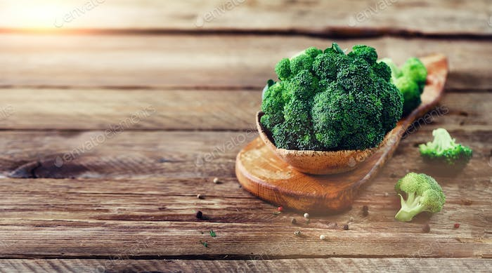 Fresh organic broccoli on wooden table close up with copyspace. Banner