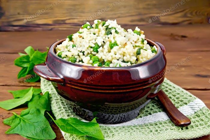Couscous mit Spinat und grünen Erbsen in Schüssel auf Holzbrett