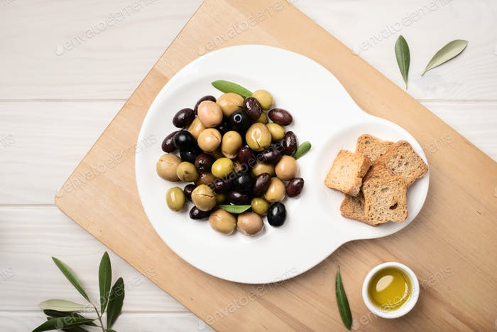 Marinierte Oliven in Platte auf Holztisch