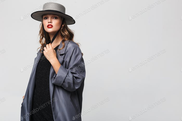 Beautiful pensive girl with wavy hair in hat and cloak dreamily looking in camera at studio
