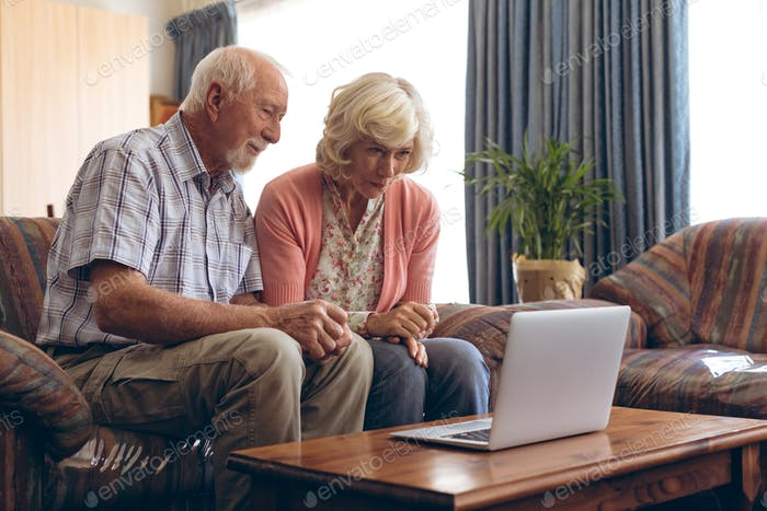 Front view of happy senior Caucasian couple making video call on laptop at retirement home