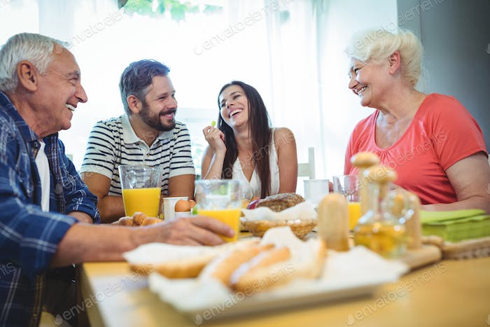 Happy couple having breakfast with their parents