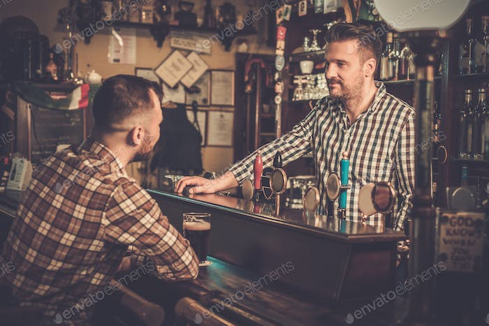 Handsome bartender talking with customer at bar counter in a pub.