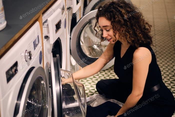Hermosa chica de ensueño cargando ropa en lavadora en lavandería de autoservicio