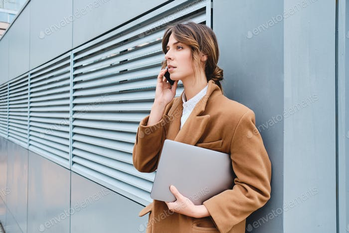Side view of serious businesswoman in coat with laptop talking on cellphone outdoor