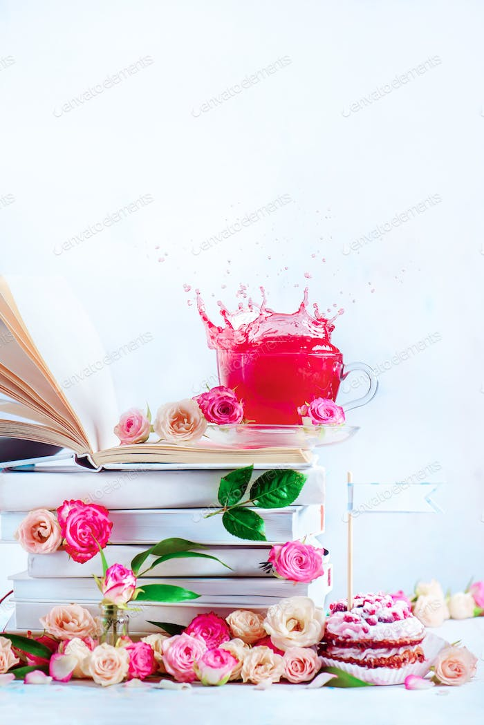 Herbal tea on a stack of white books with a dynamic splash. Romantic still life with copy space