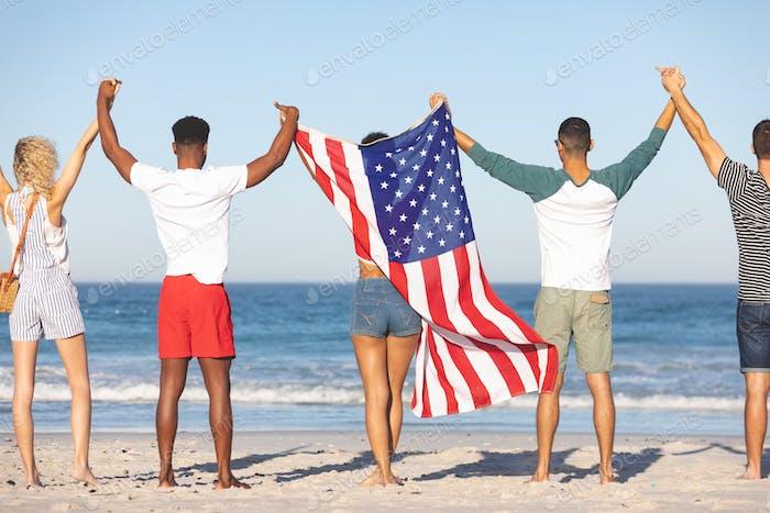 Rückansicht von verschiedenen Freunden zusammen mit amerikanischer Flagge stehen und Hände heben am Strand
