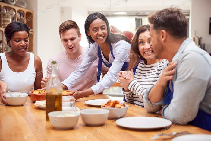 Group Of Friends Sitting Around Table Eating Meal At Home Together