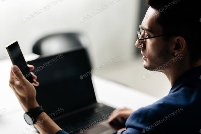 Professional architect in glasses dressed in blue checkered uses the phone near the desk with laptop