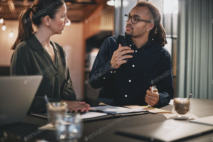 Two businesspeople going over paperwork together in an office
