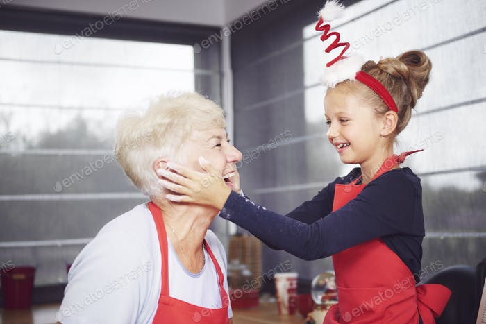 Granddaughter rubbing flour on grandmother's face