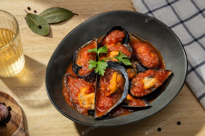Cooked Mussels with tomato sauce on plate