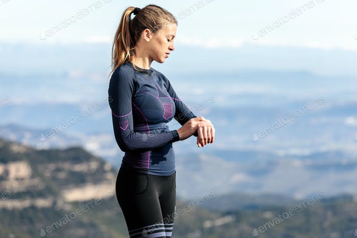 Trail runner using her smartwatch while relaxing one moment on m
