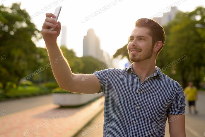 Young handsome man taking selfie with mobile phone in park