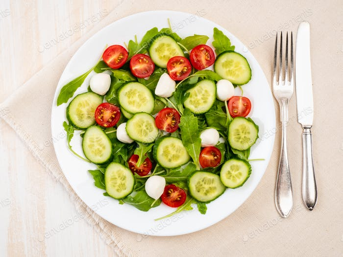 Fresh salad with tomatoes, cucumbers, arugula, mozzarella. Oil with spices, top view