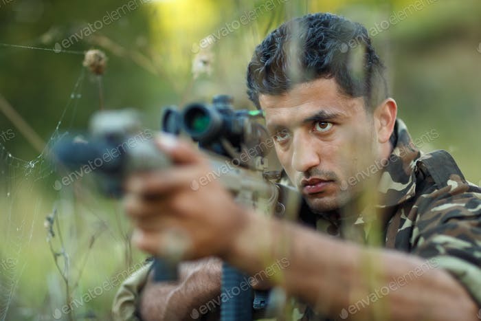 Man of Arab nationality in camouflage with a gun aiming at a tar