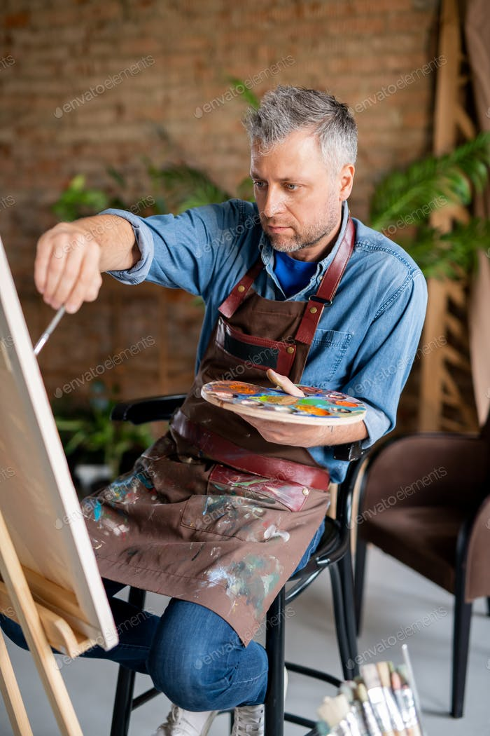 Concentrated professional painter with palette working over new painting