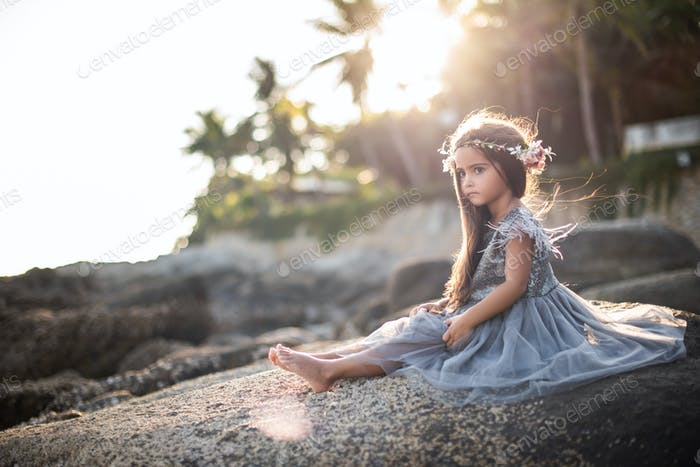 Beautiful preteen girl in dress on shore in thailand in daytime