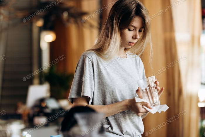A youthful pretty blonde girl,dressed in casual style, holds a clean glass and looks at it in a