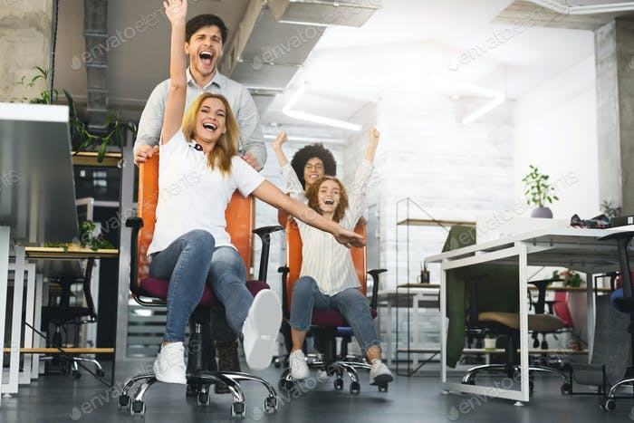 Overjoyed millennial colleagues racing on office chairs