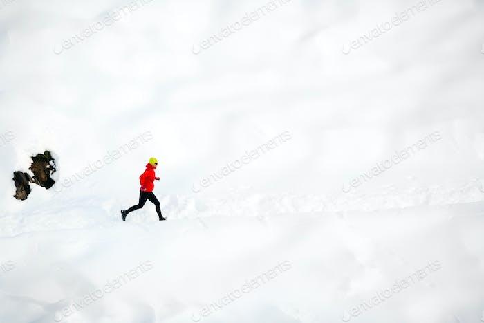 Женщина бежит по снегу в горах