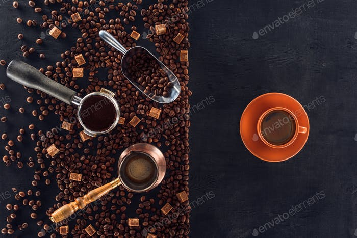 top view of roasted coffee beans, scoop, coffee pot, coffee tamper and cup of coffee on black