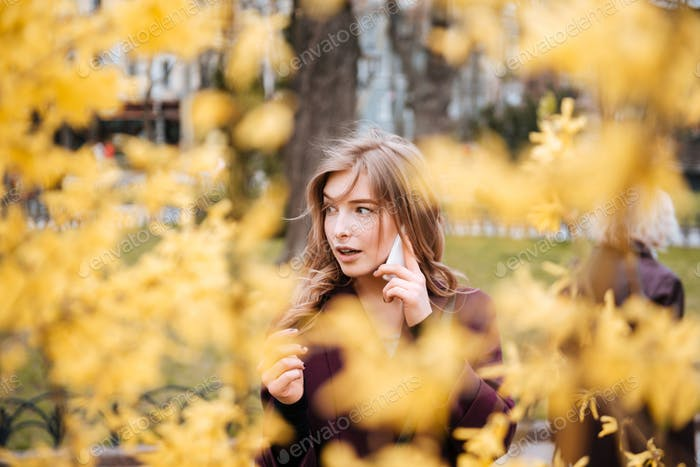 Attractive young woman talking on cell phone in park
