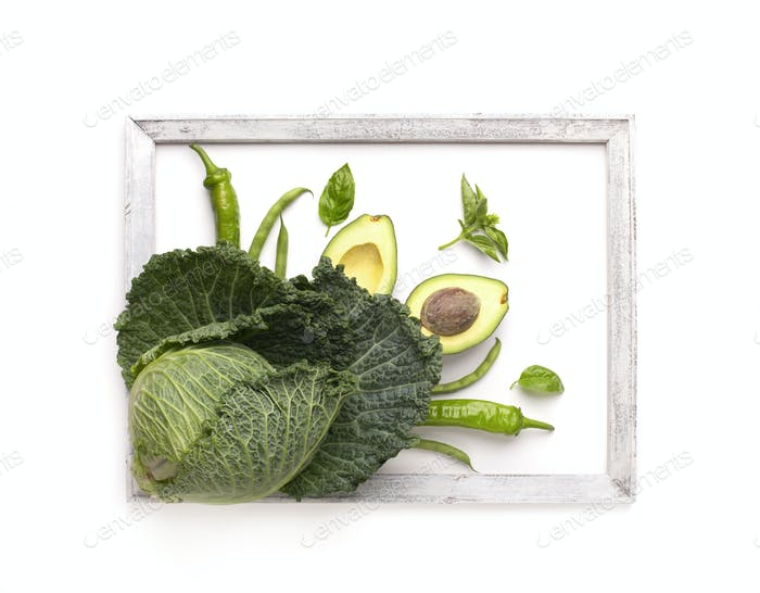 Green vegetables decorating white background and surrounded by wooden frame
