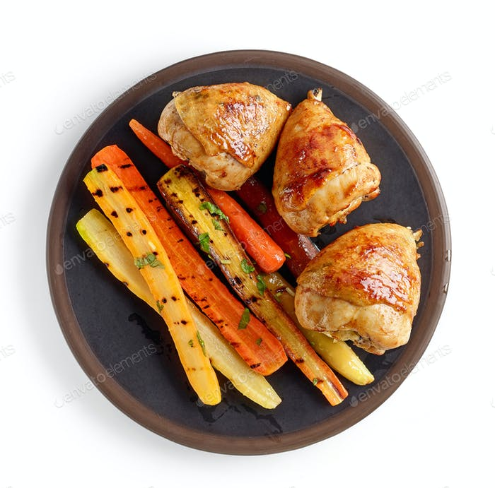 plate of grilled chicken legs and carrots