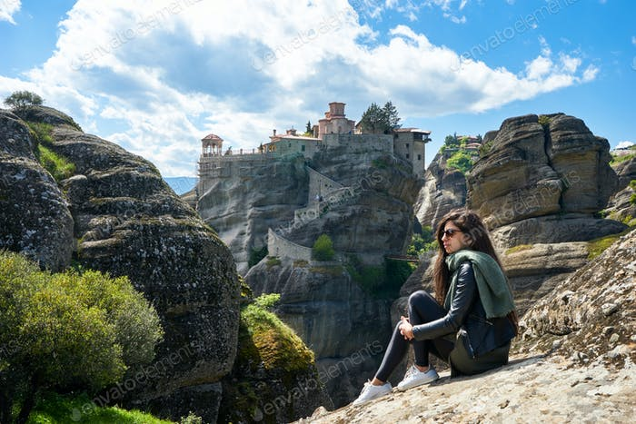 Girl enjoys the view of great Monastery of Varlaam on the high r
