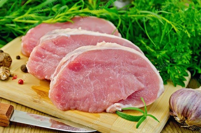 Fleisch Schweinefleisch Scheiben auf einem Brett mit Grüns