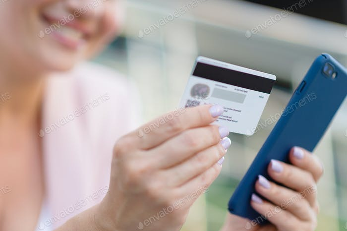 Mujer de negocios con una tarjeta de crédito y teléfono hace compras al aire libre.