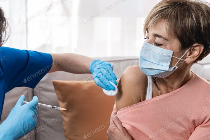 Krankenschwester gibt Seniorin im Haus während der Lockdown-Isolierung Coronavirus-Impfstoff