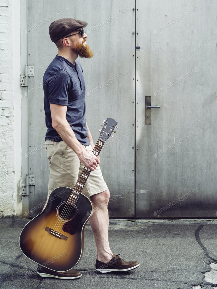 Bearded man walking with acoustic guitar