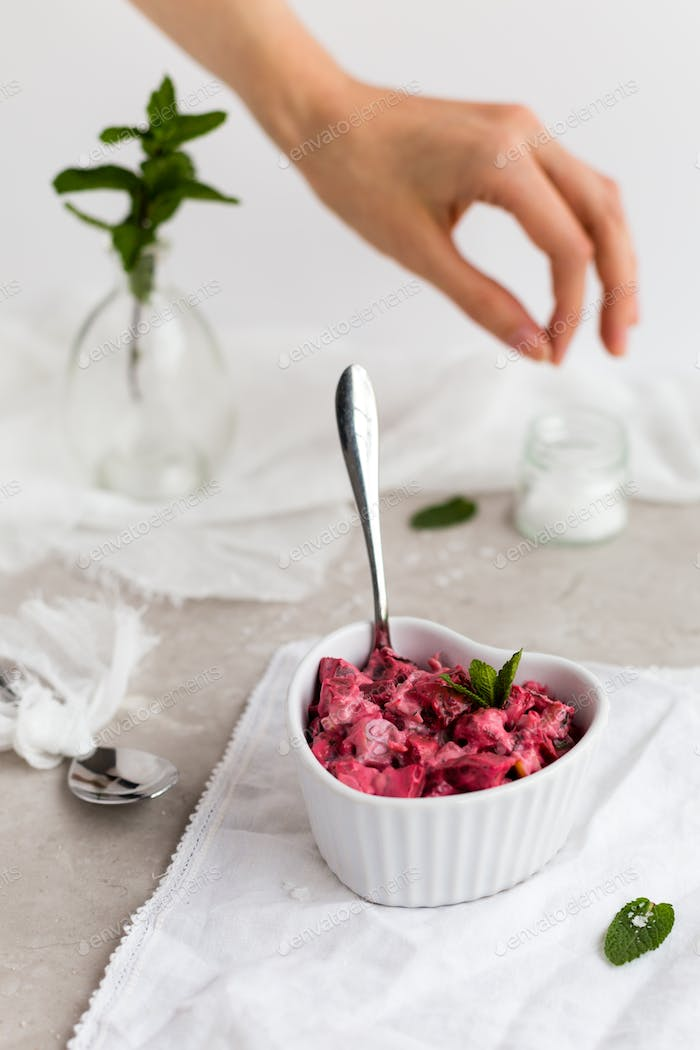Beetroot Dip in White Dish with Female Hand Seasoning in Background