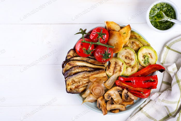 Grilled vegetables and green pesto on light background, top view. Tasty vegetarian snack
