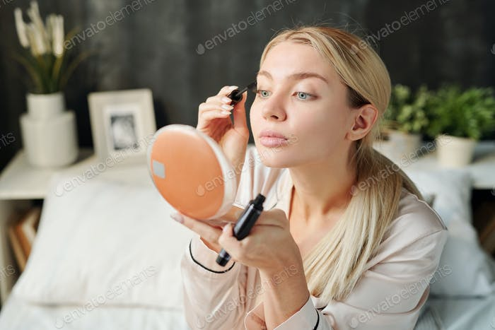 Pretty woman with long blond hair applying black mascara on eyelashes