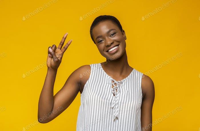 Smiling black girl posing at camera and demonstrating v-sign
