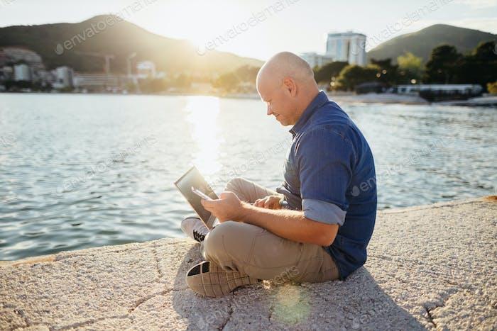 freelancer browsing laptop on beach