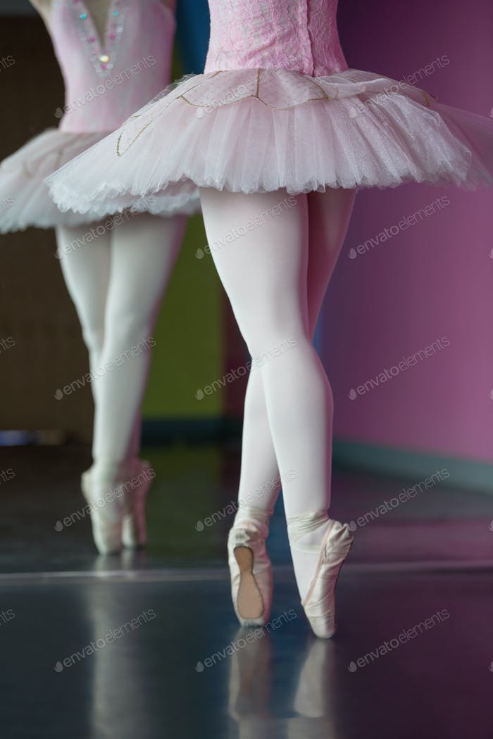 Graceful ballerina standing en pointe in front of mirror in the ballet studio