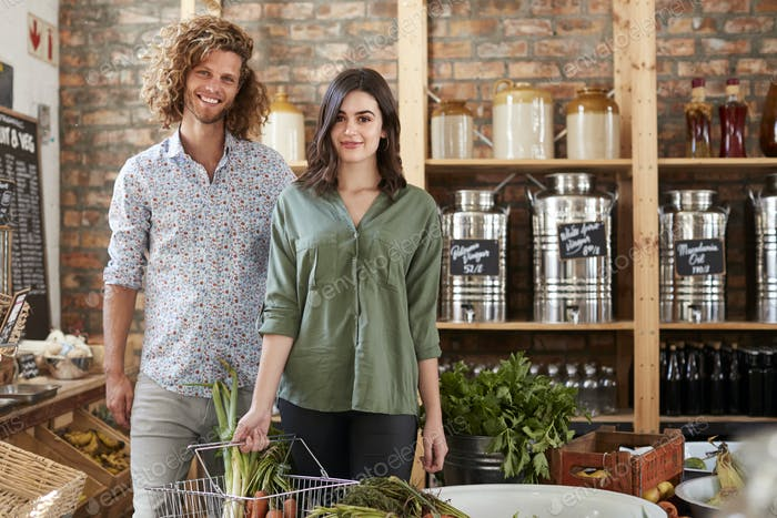 Portrait Of Couple Buying Fresh Fruit And Vegetables In Sustainable Plastic Free Grocery Store