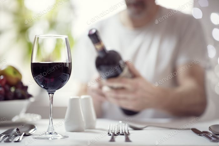 Man reading a wine bottle label in restaurant