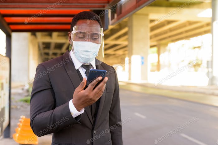 African businessman with mask and face shield using phone at the bus stop in the city outdoors