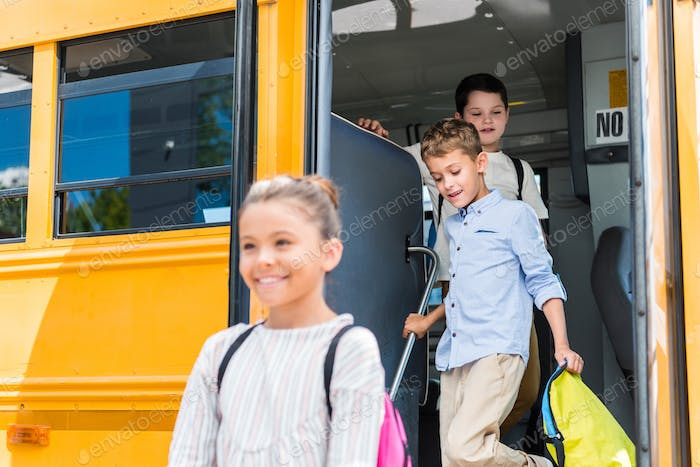 adorable scholars going out of school bus