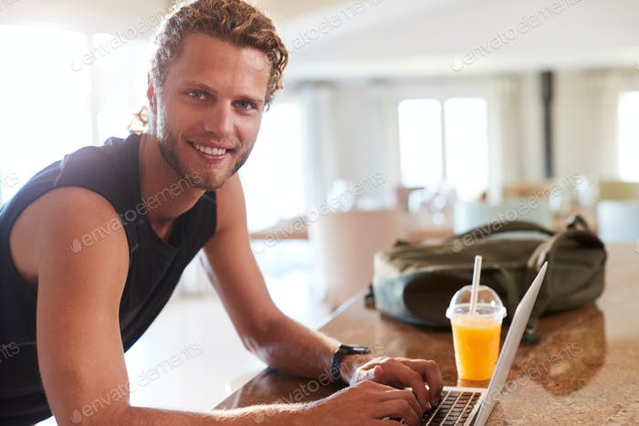 Millennial white man checking fitness app on laptop at home after a workout, smiling to camera