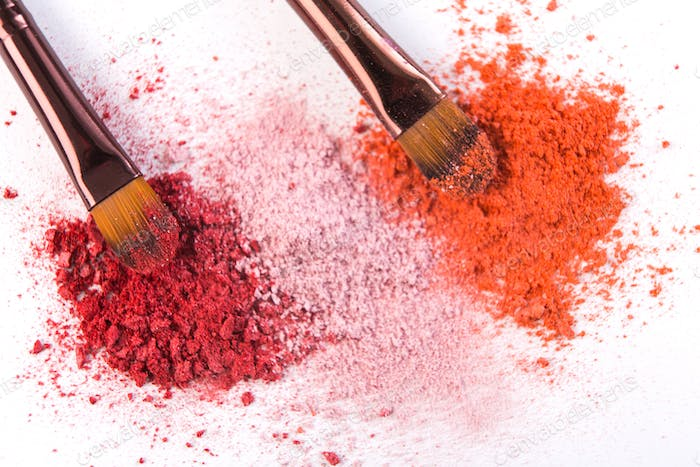 Makeup brushes with blush or eyeshadow of pink, red and coral tones sprinkled on white background