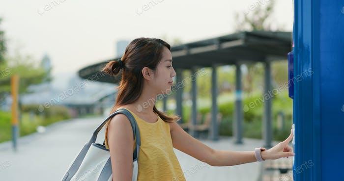 Frau benutzt Handy, um im Freien ein Getränk zu kaufen