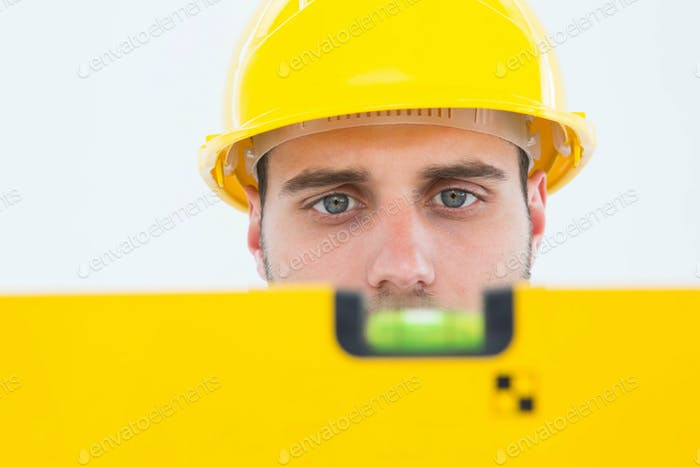 Close-up of male technician using spirit level on white background