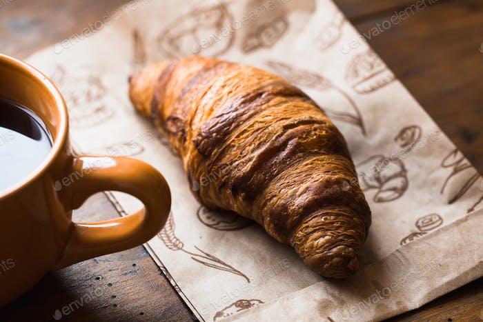 Kaffee-Croissant auf alten Holztischhintergrund