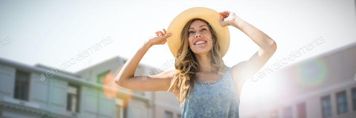 Imagen compuesta del retrato de una mujer tocando su sombrero de paja